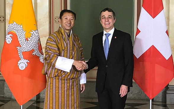 Ignazio Cassis shakes hands with the traditionally dressed foreign minister of Bhutan, Tandi Dorji. They are standing in front of the two states' flags.