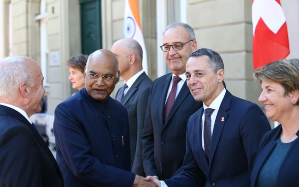The Indian President and Ignazio Cassis shake hands in the presence of the entire Federal Council.