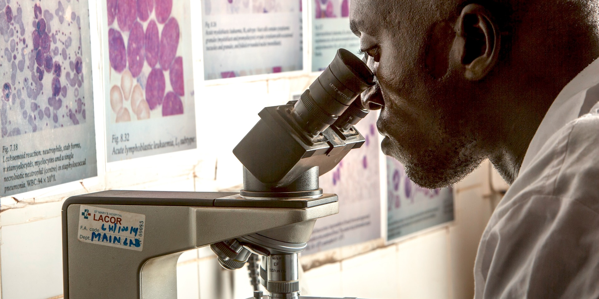 An employee in a hospital looks through a microscope.