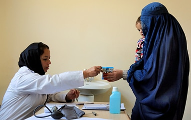 A mother with her child in her arms receives medication from a hospital employee in Kabul, Afghanistan.