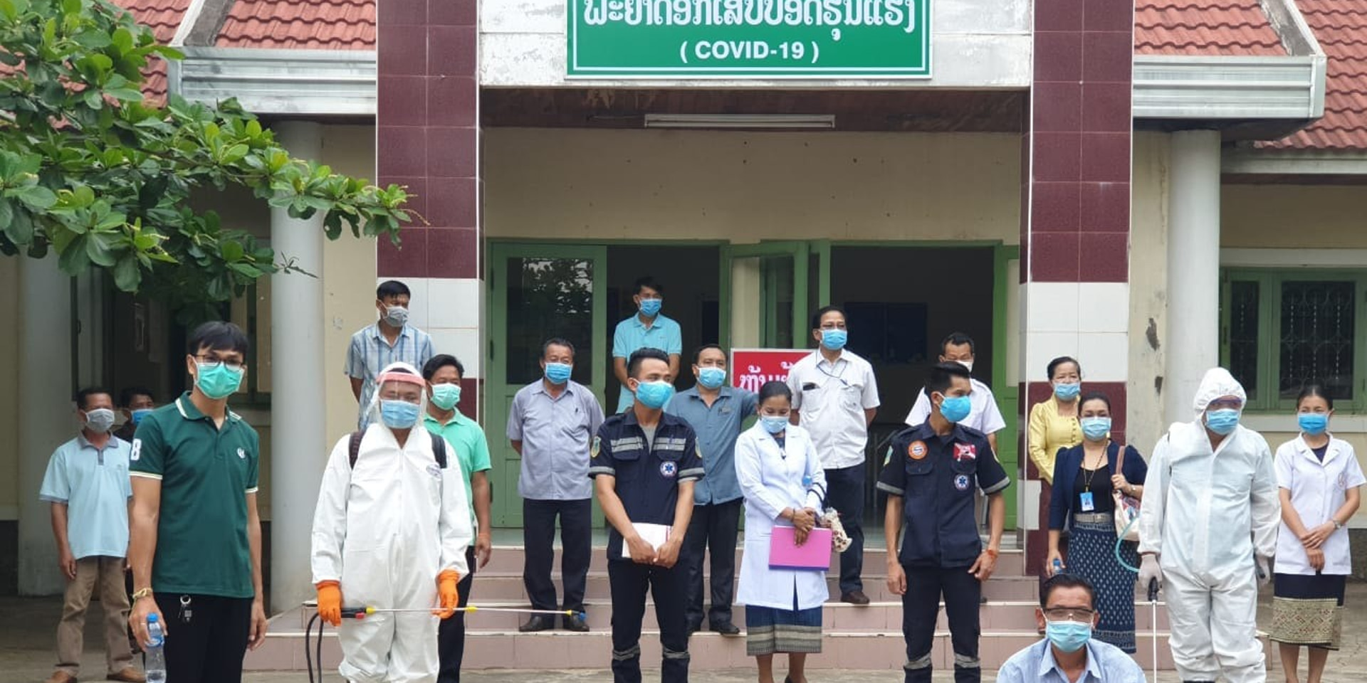 The staff of a hospital in Laos stand in front of the entrance to a COVID-19 ward wearing protective masks.