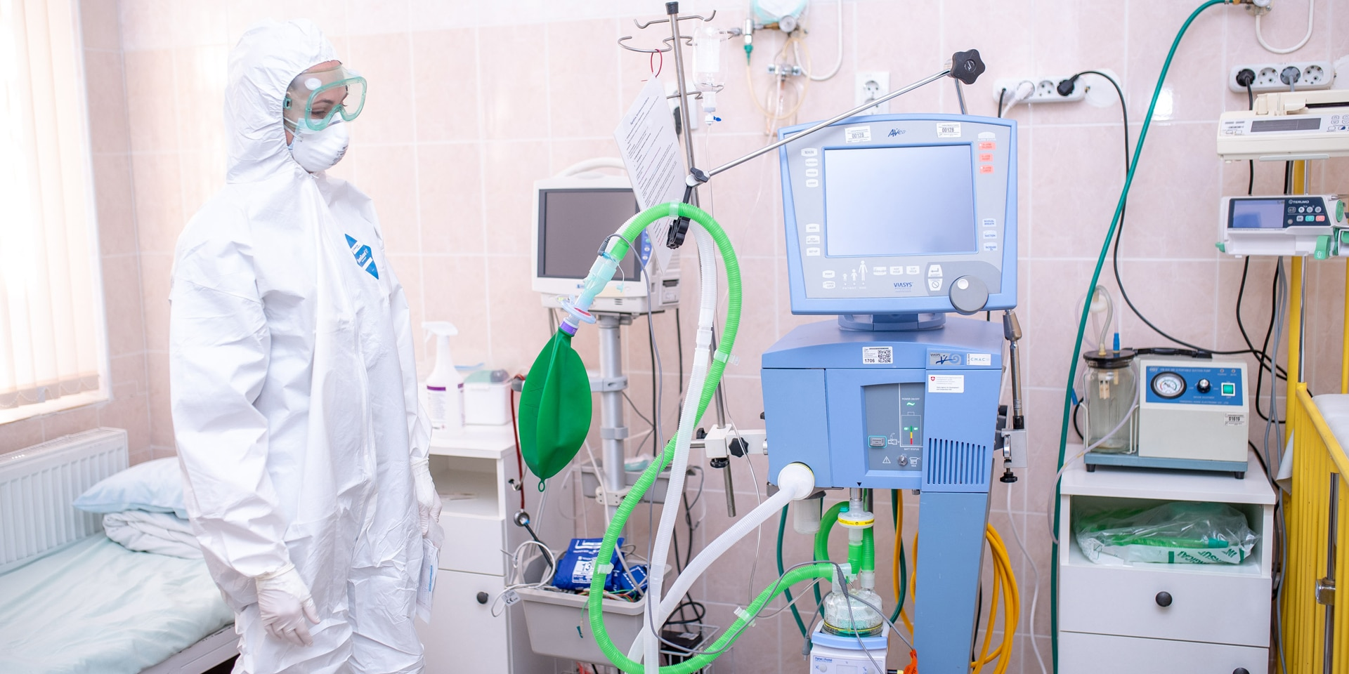 A nurse in protective clothing stands next to a ventilator used to treat acute COVID-19 cases.
