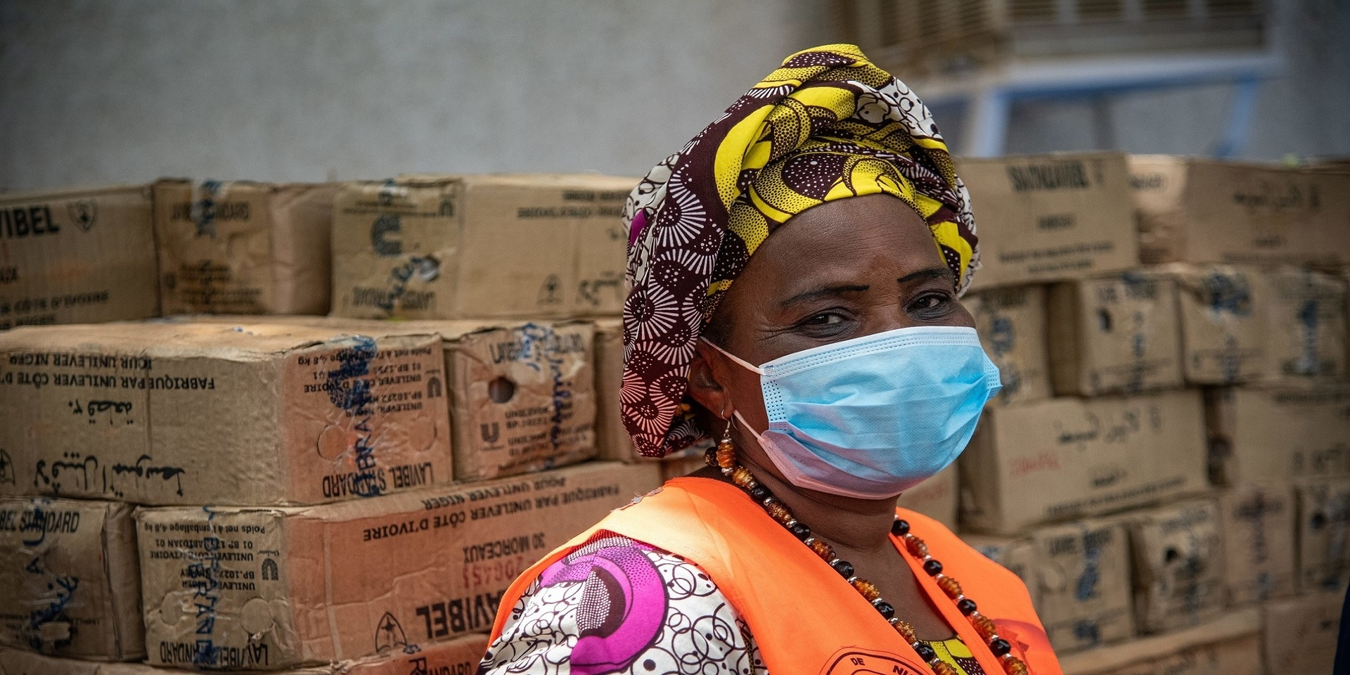 An African woman wearing a mask and an orange vest in a warehouse stacked with boxes