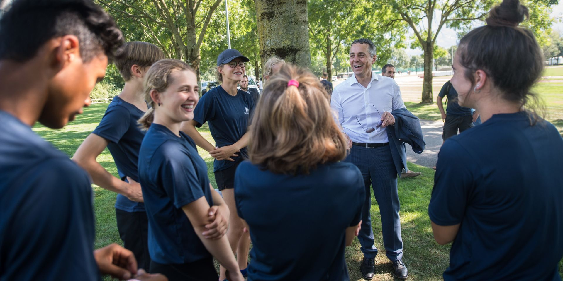 Federal Councillor Ignazio Cassis in conversation with track and field athletes during training.