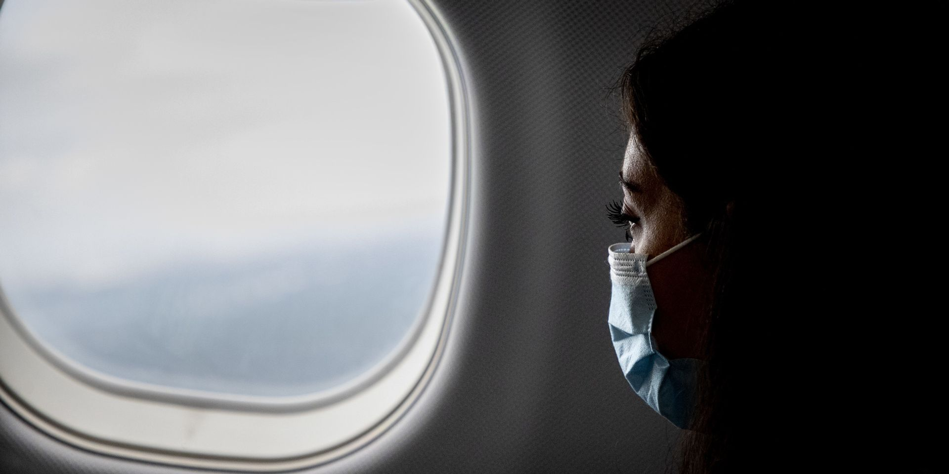 A woman with a face mask is looking out the airplane window.
