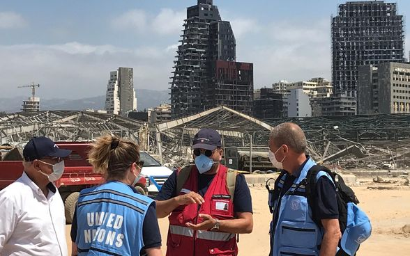 A member of the expert groups of Switzerland's humanitarian aid in discussion with UN experts. In the background the destroyed city.