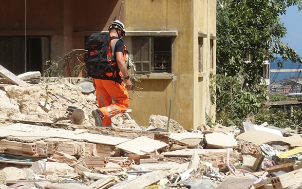 A member of the Swiss Humanitarian Aid Unit walks over the debris of a building.