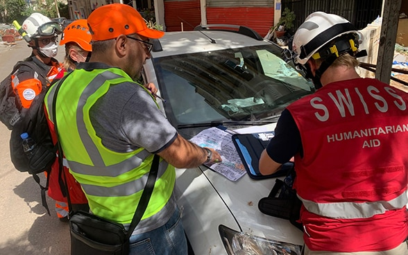 Four people stand by a damaged car and discuss a local map.