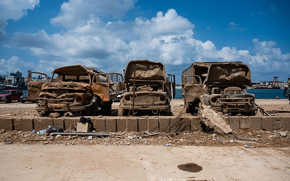 Three destroyed vehicles stand in the port of Beirut.