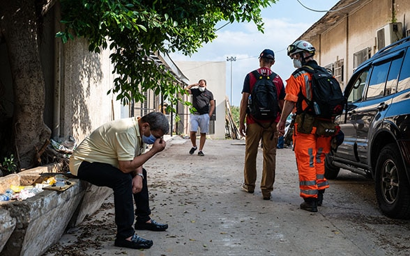 A man is sitting desperately on the side of the road with his head in his hands. Experts from the Swiss Humanitarian Aid Unit walk past him.