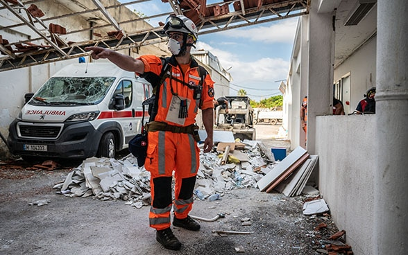 An expert from the Swiss Humanitarian Aid Unit is standing in the debris of a hospital.