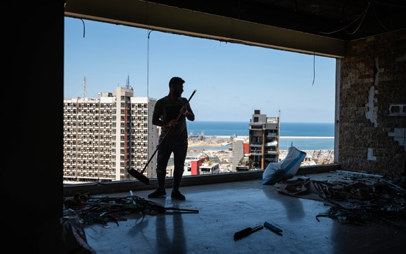 A resident cleaning the destroyed living space in an apartment building overlooking the port of Beirut.