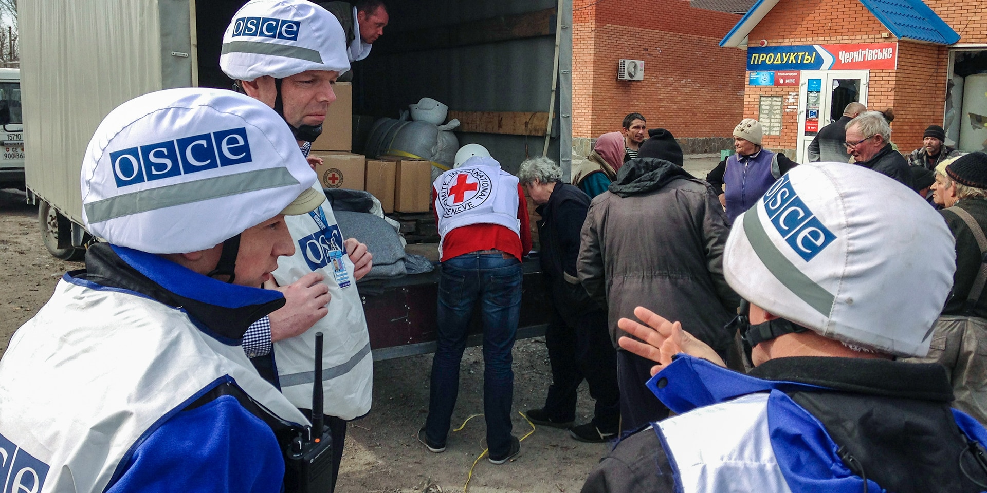 Three members of the OSCE mission observe the delivery of aid packages to the Ukrainian population.