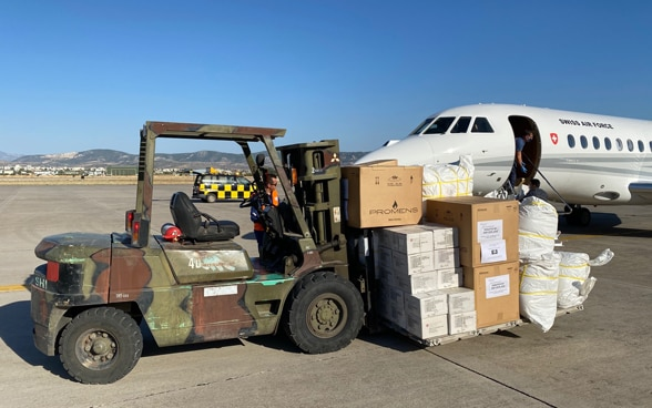 A forklift truck transports boxes and bags of relief supplies away from the aircraft.