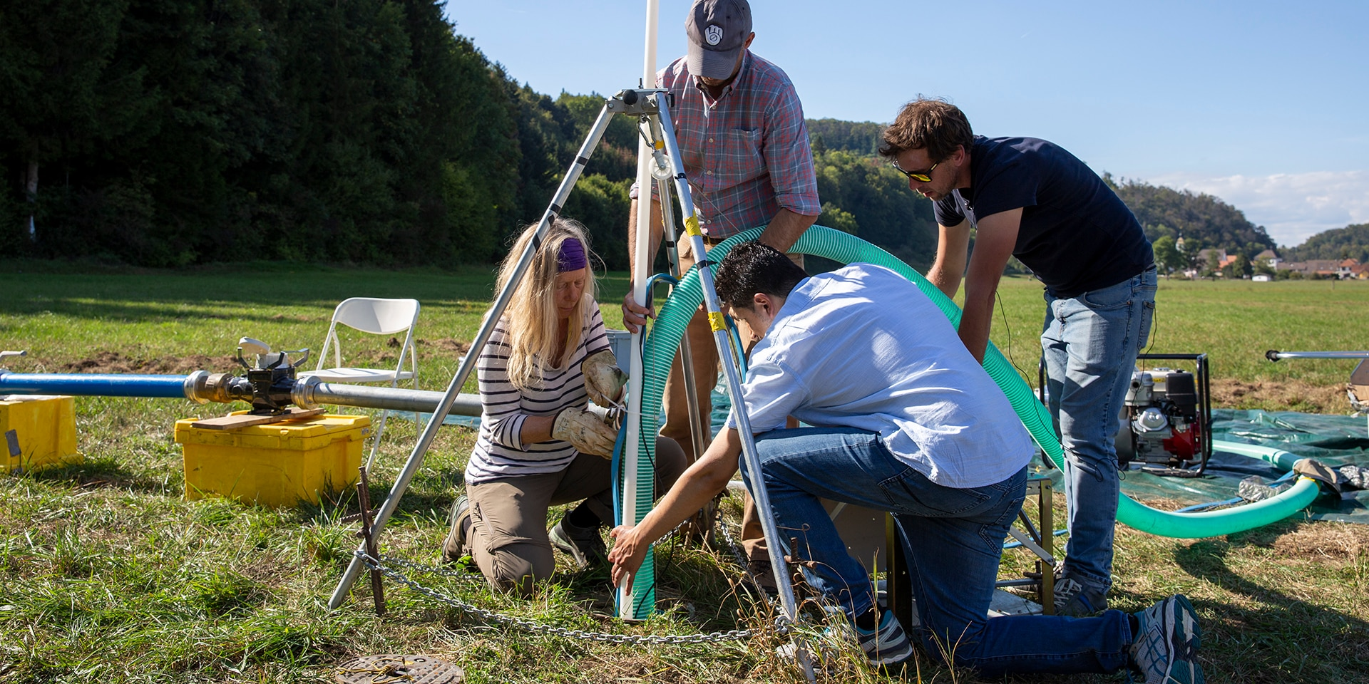 On a meadow, four experts from the Swiss Humanitarian Aid Unit are laying a water pipe in a hole in the ground.