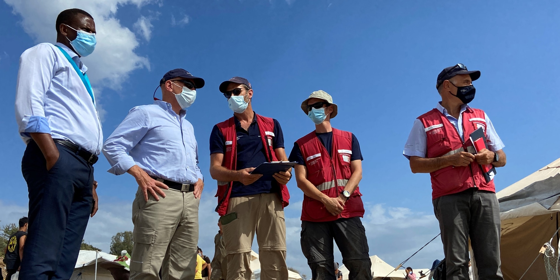 The Head of Switzerland's Humanitarian Aid Department Manuel Bessler talks to members of the Swiss Humanitarian Aid Unit and Spiros Habimama, deputy director of the Lesbos camp, during a site visit.
