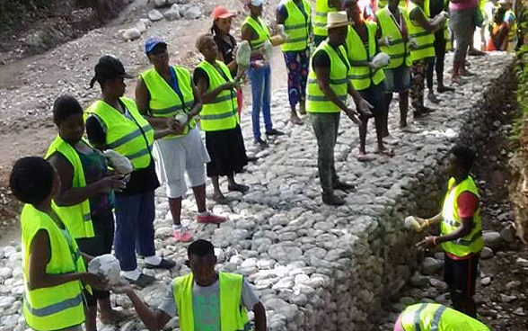Several people wearing yellow safety waistcoats are building new gabions with stones.