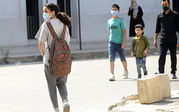 A young girl wears a mask and goes to school with her backpack on.