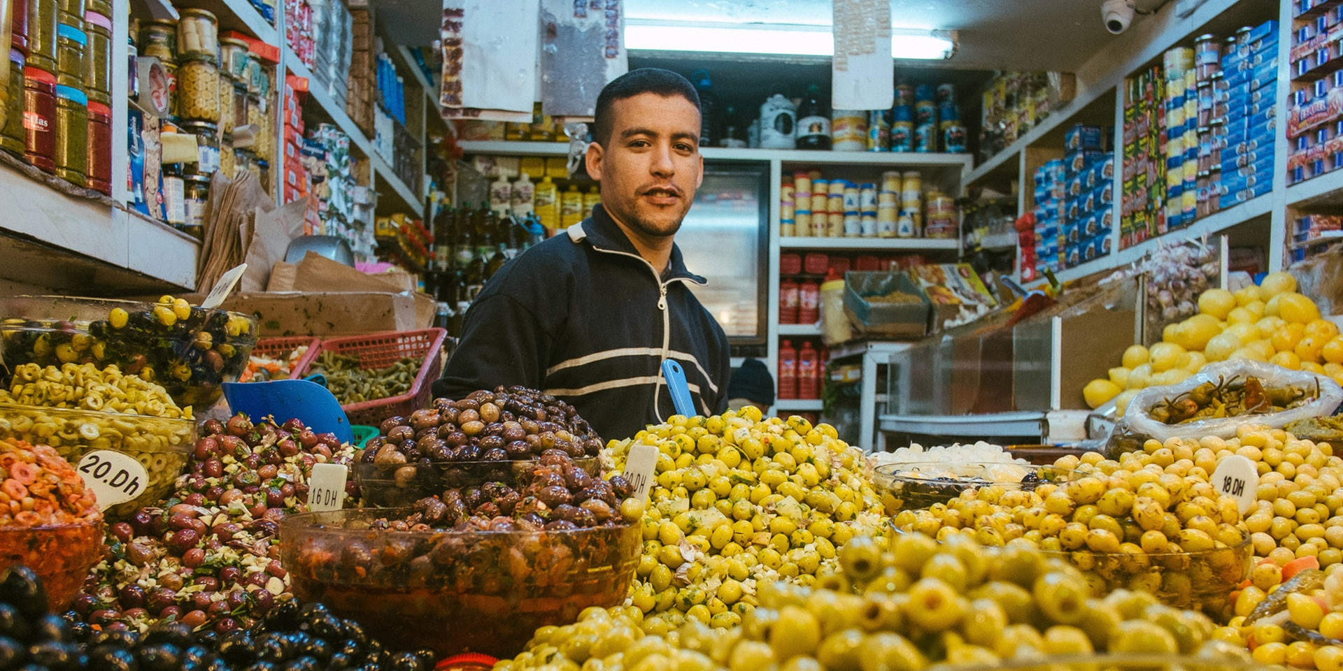 An olive seller stands in a small shop in front of a large display of olives of all kinds.