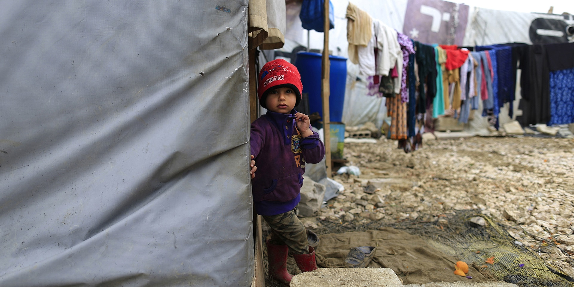 A Syrian refugee boy stands outside his family's tent after heavy rain.