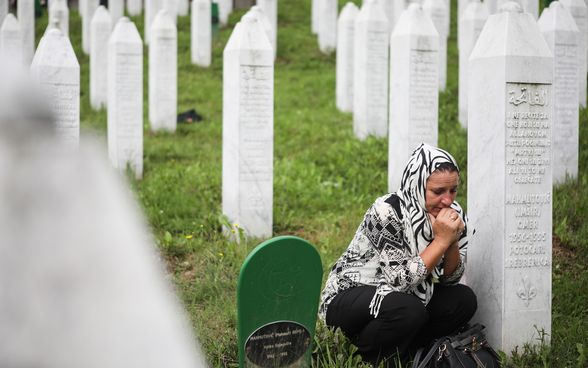 A woman kneels beside a memorial stone at the cemetery in Srebrenica.