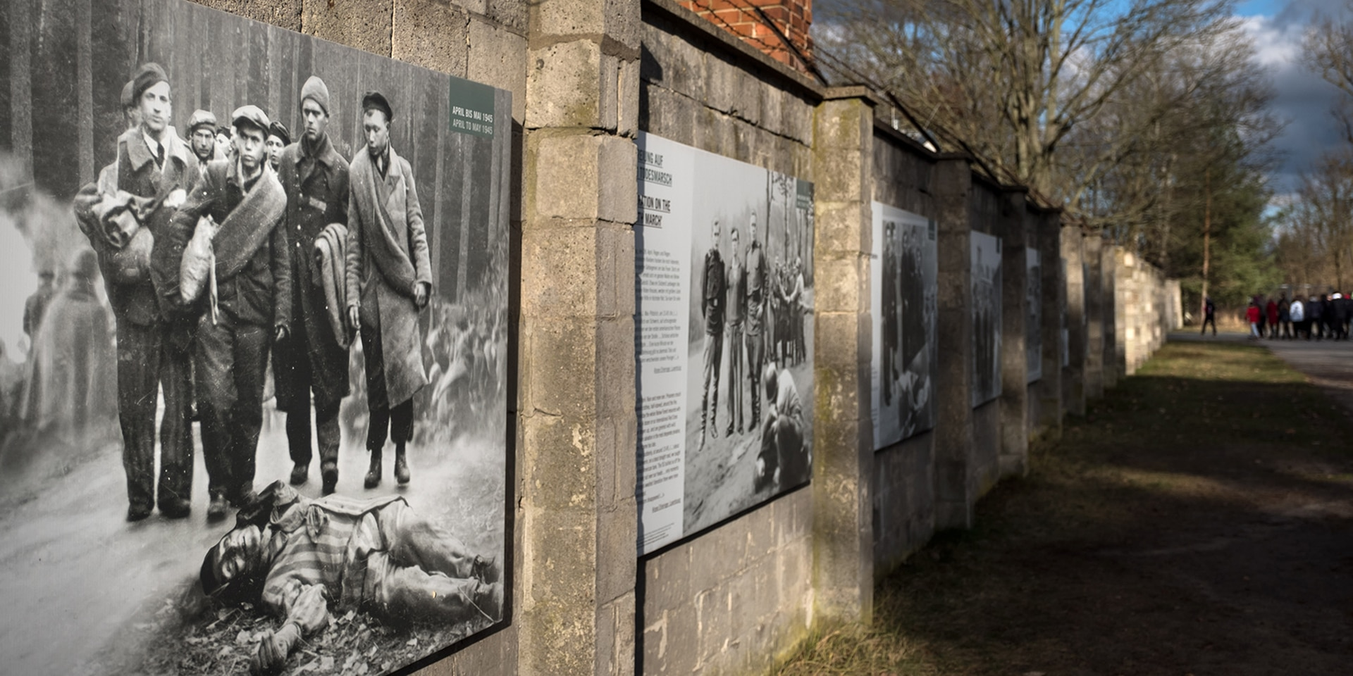 Wall at the Sachsenhausen Concentration Camp Memorial displaying pictures of the camp and information.