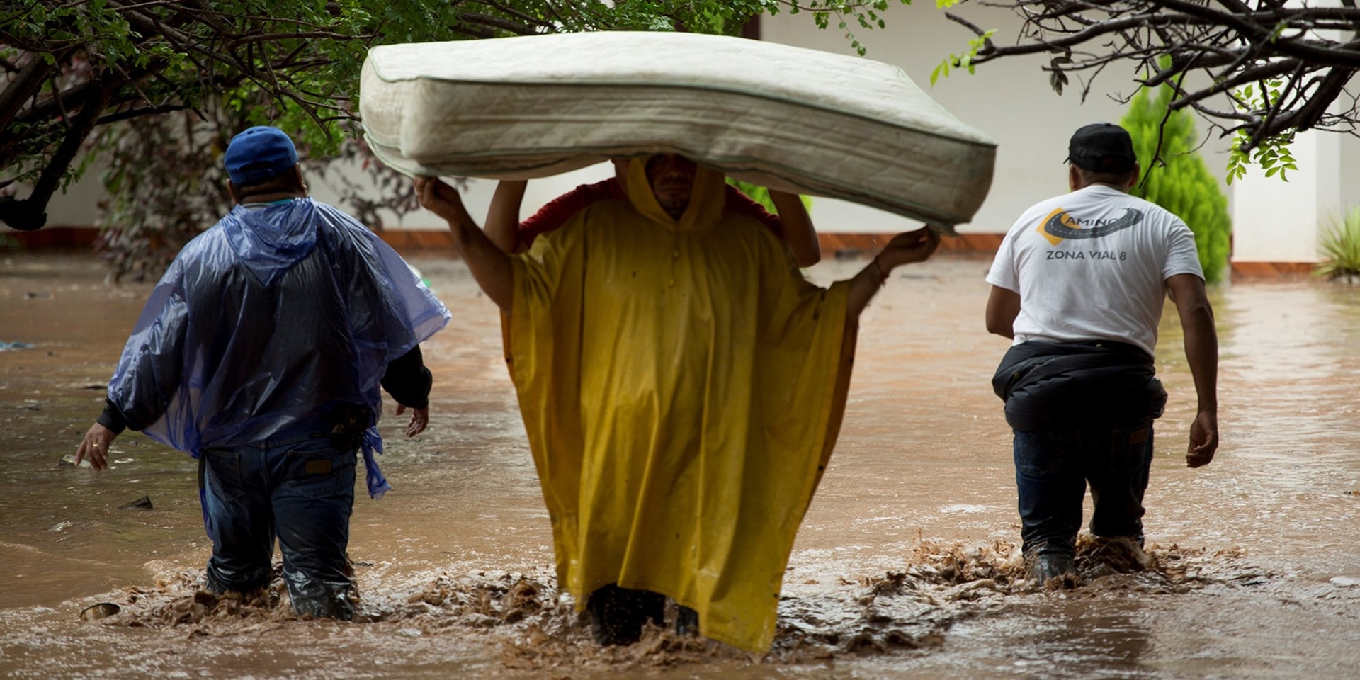 Two people carrying a mattress through the floods, accompanied by two aid workers.