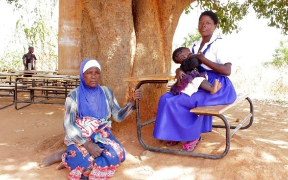A woman sitting on the ground in the shade of a tree. Another woman sitting at a school desk next to her cradling a child.