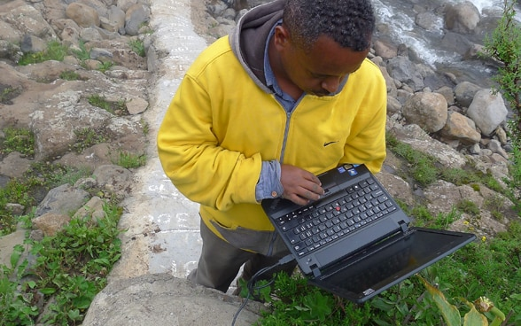 Man standing by a river using a laptop.