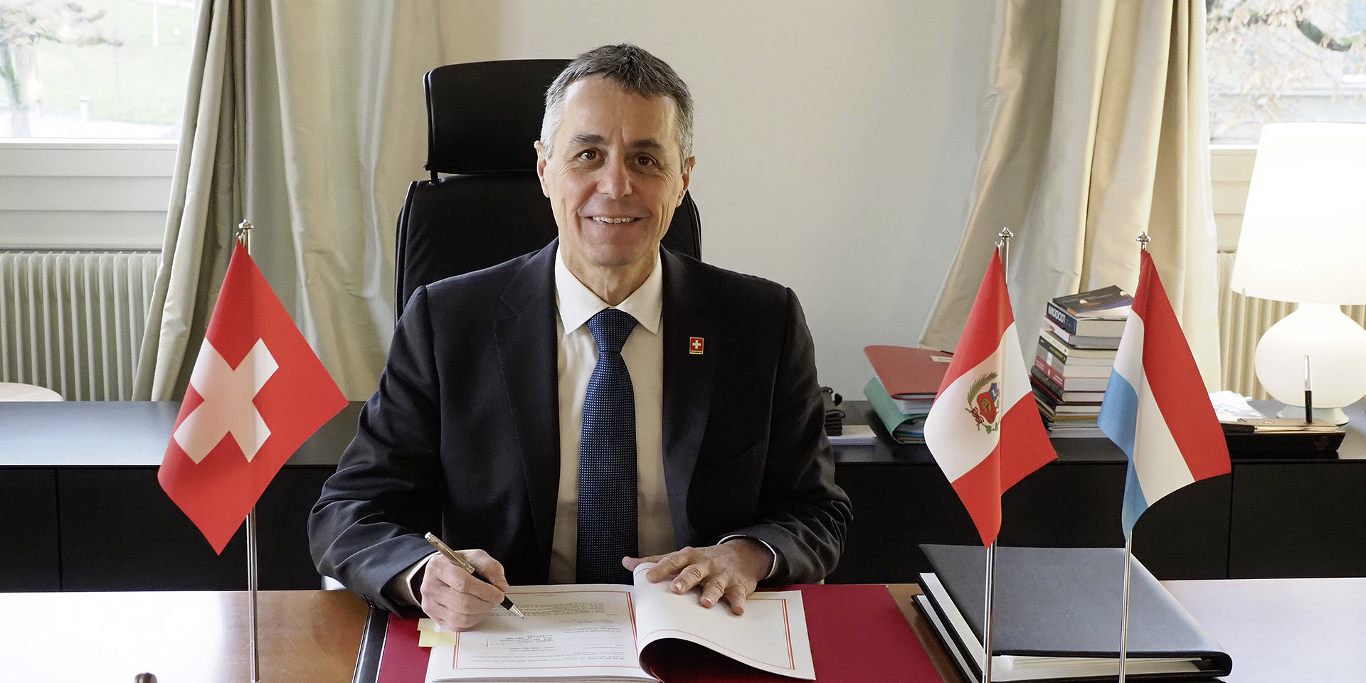 Federal Councillor Ignazio Cassis signs a document. On his desk appear the flags of Switzerland (on his right), Peru and Luxembourg (on his left).