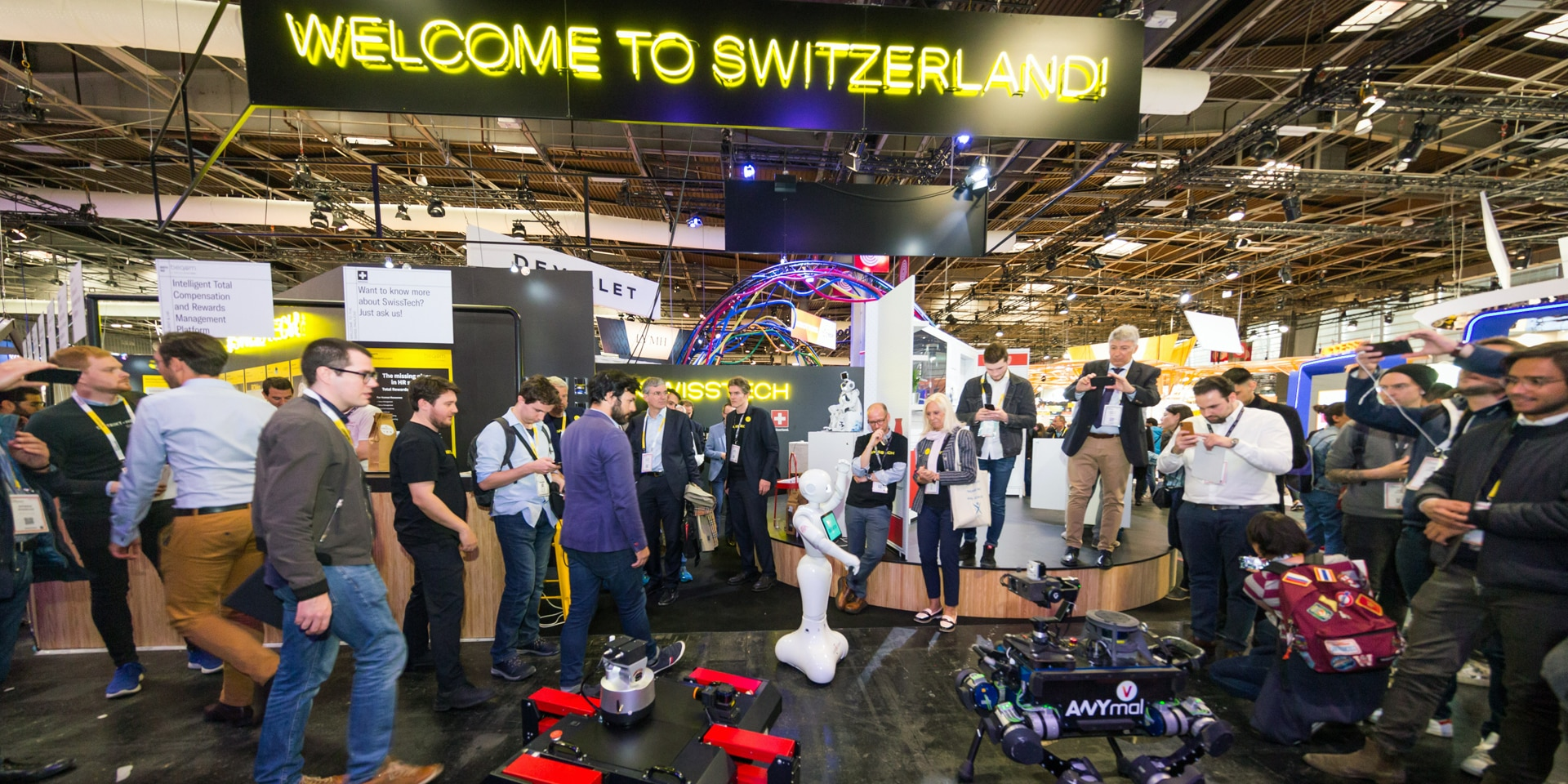 "In an exhibition hall, people look at drones, robots and innovative technologies. Above them is a sign reading ""Welcome to Switzerland""."