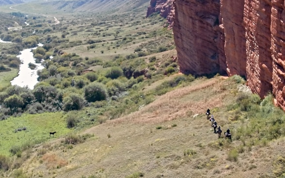 Five riders trek along a rock face in a remote valley.