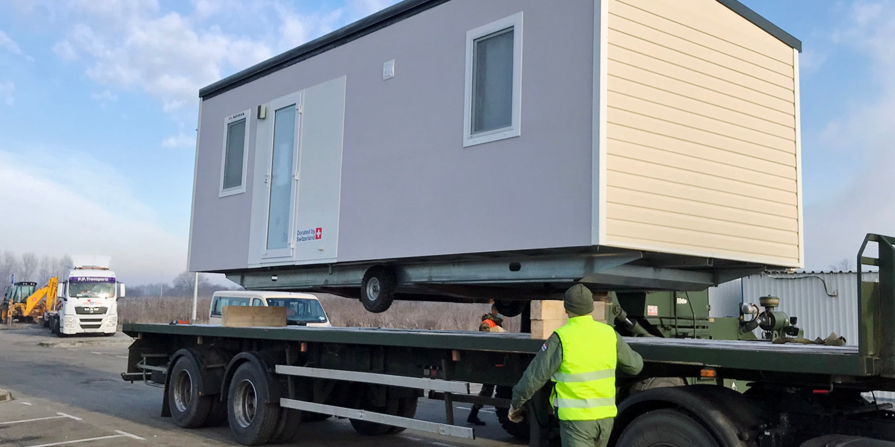 A mobile housing unit is transported by truck.