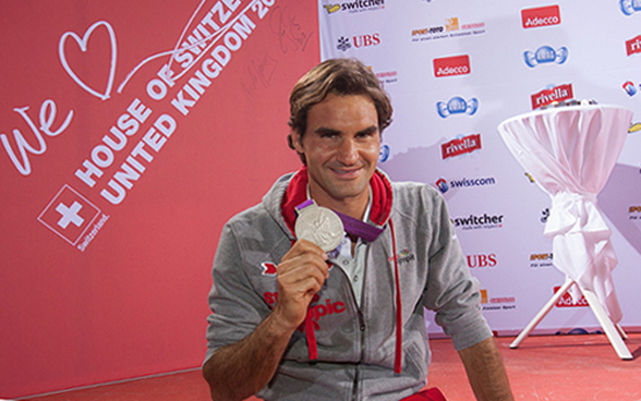 Roger Federer holding up his Olympic medal