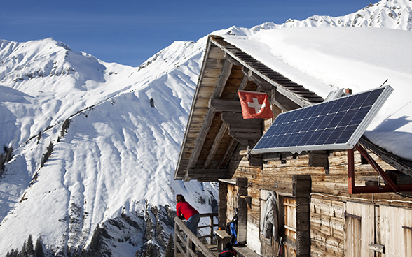 Solar panel next to a mountian hut in winter
