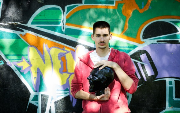 A young man standing in front of a graffiti-covered wall, holding a sculpture of a head in his hands.