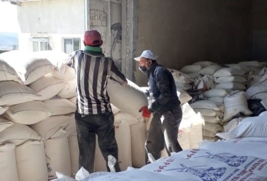 two men are stockpiling sacks