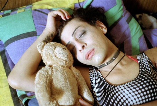 a transgender woman lying in bed with a teddy bear