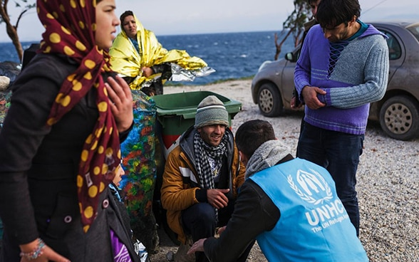 A UNHCR employee welcomes refuges on a shore.