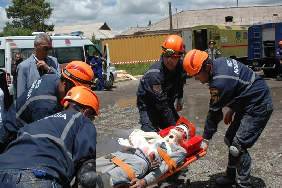 a simulated casualty is evacuated on a stretcher as part of a rescue exercise.