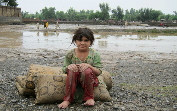 A girl in Pakistan sitting on a pillow outside in front of a puddle of water.