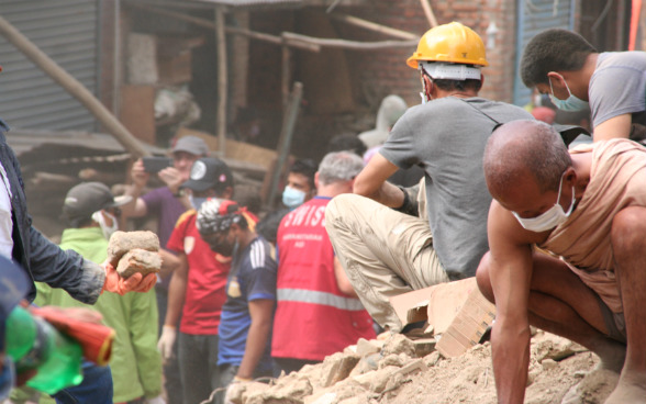 People clearing away the rubble from a collapsed building.