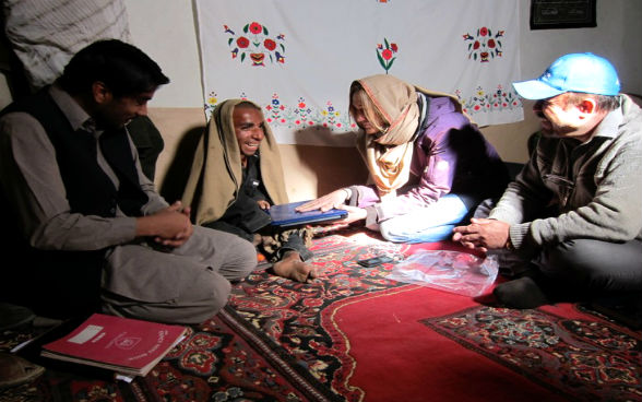 A woman and two men sitting in a tent as the woman hands over a laptop to one of the men.