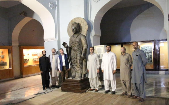 Several men stand on either side of the Buddha statue in a hall at the Peshawar Museum.