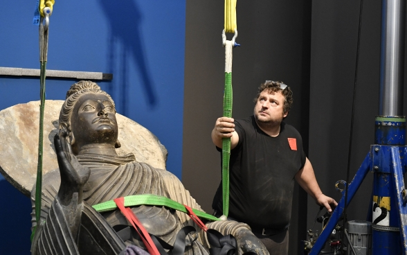 A Rietberg Museum employee oversees the Buddha sculpture, hanging by two straps from a crane, being hoisted upright.
