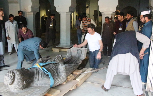 The Buddha statue is laid down on wooden pallets to transport it out of the museum's exhibition hall. A number of people stand by and watch.
