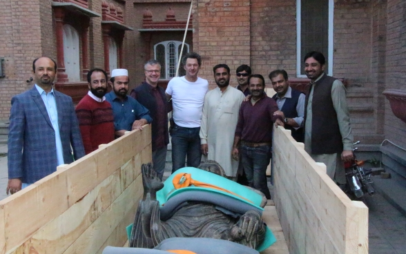 The Buddha sculpture lies in an open wooden crate securely fastened. The museum staff from Switzerland and the team from Pakistan pose for a group photo around it.