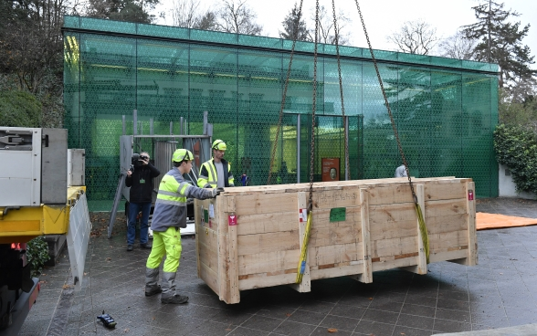 The shipping crate is supported by chains and unloaded by a crane in front of the glass facade of the Rietberg Museum.