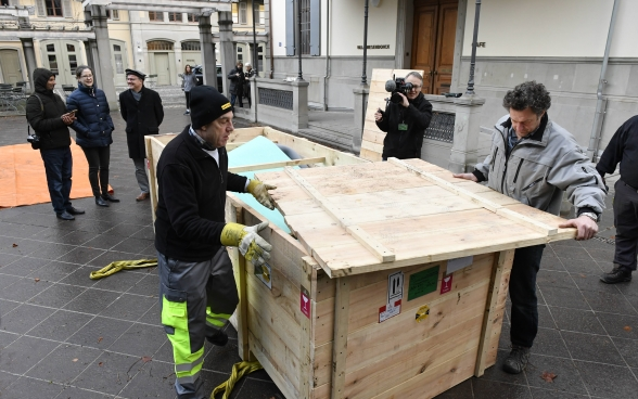 Two men remove the top of the wooden shipping crate.