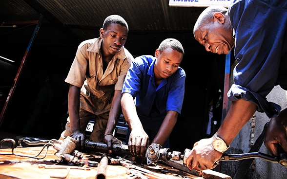 Three men working together on an engine.